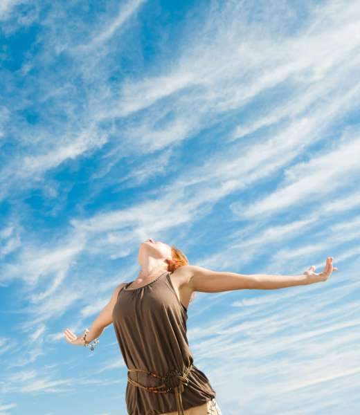 Beautiful young dancer performing yoga-dance outdoors with blue sky and clouds in the background